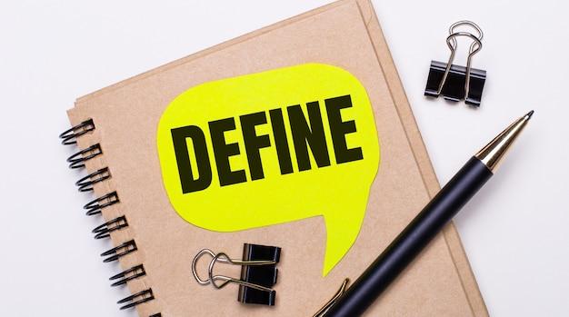 Op een lichte ondergrond een bruin notitieboekje, een zwarte pen en paperclips en een gele kaart met de tekst define. bedrijfsconcept.