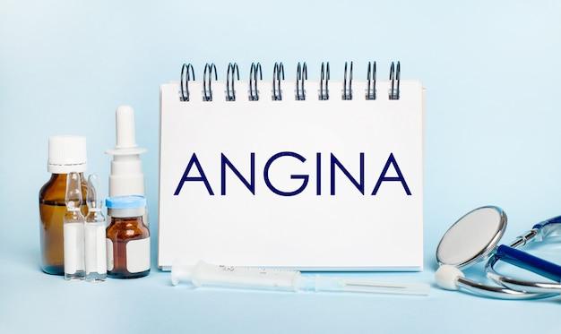 Op een lichte ondergrond een injectiespuit, een stethoscoop, medicijnflesjes, een ampul en een wit notitieblok met de tekst angina. medisch concept