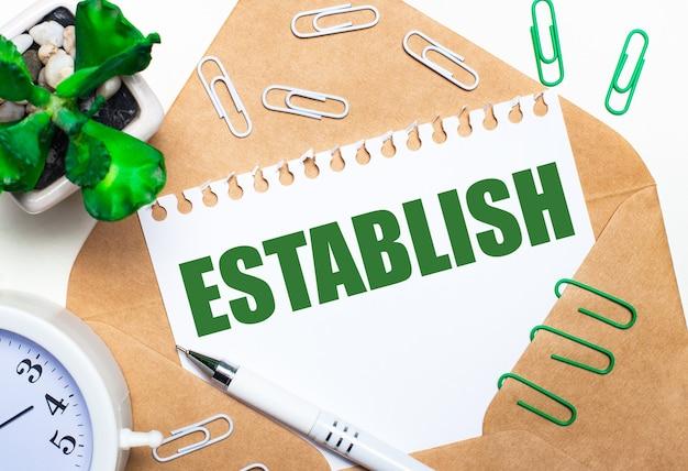 Op een lichte ondergrond een open envelop, een witte wekker, een groene plant, witte en groene paperclips, een witte pen en een vel papier met de tekst vaststelling