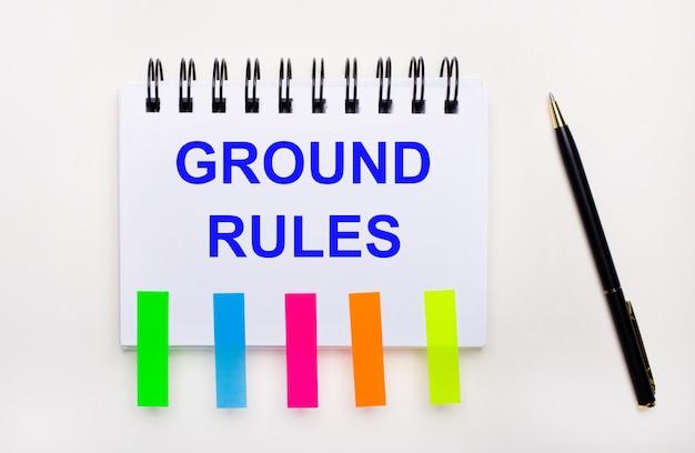 Op een lichte ondergrond een pen, een notitieboekje met de tekst ground rules en felle stickers.