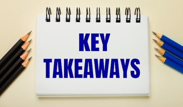 Op een lichte ondergrond een wit notitieboekje met de tekst key takeaways en zwart-blauwe potloden aan de zijkanten.