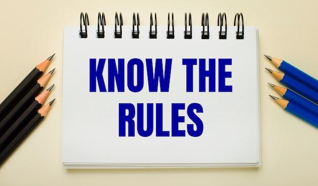 Op een lichte ondergrond een wit notitieboekje met de tekst know the rules en zwarte en blauwe potloden aan de zijkanten.