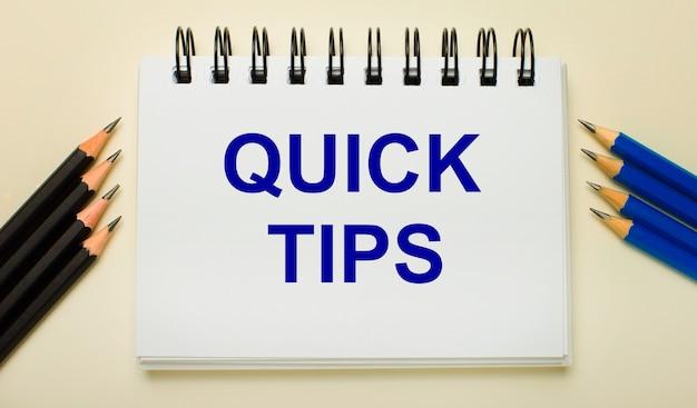 Op een lichte ondergrond een wit notitieboekje met de tekst quick tips en aan de zijkanten zwarte en blauwe potloden.