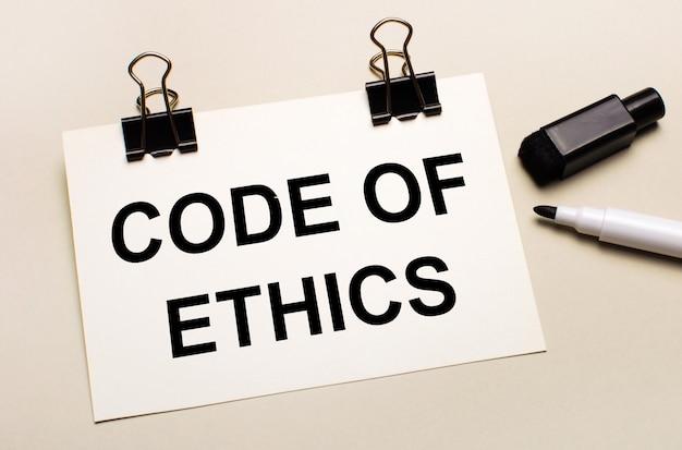 Op een lichte ondergrond een zwarte open stift en op zwarte clips een wit vel papier met de tekst code of ethics