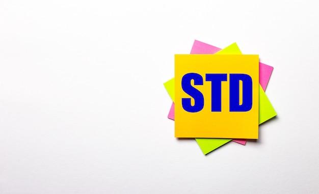 Op een lichte ondergrond - felgekleurde stickers met de tekst std