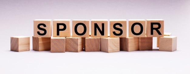 Op een lichte ondergrond houten kubussen met de tekst sponsor