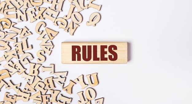 Op een lichte ondergrond houten letters en een houten blok met de tekst rules. plat leggen