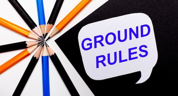 Op een lichte ondergrond veelkleurige potloden en op een zwarte ondergrond een witte kaart met de tekst ground rules.
