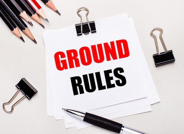Op een lichte ondergrond zwarte potloden, zwarte paperclips, een pen en een vel wit papier met de tekst ground rules.