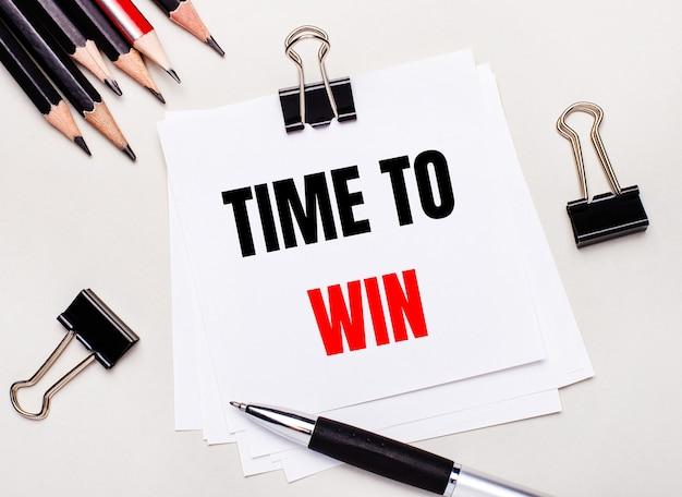 Op een lichte ondergrond zwarte potloden, zwarte paperclips, een pen en een vel wit papier met de tekst time to win.
