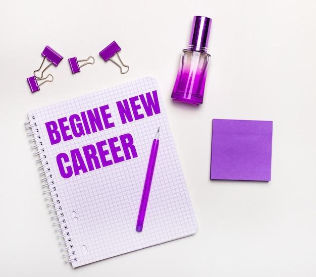 Op een lichte tafel - een lila geschenk, parfum, lila zakelijke accessoires en een notitieboekje met een lila inscriptie begin nieuwe carrière. plat leggen. het bedrijfsconcept van vrouwen