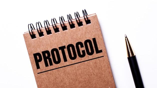 Op een lichte tafel, een zwarte pen en een bruin notitieboekje op zwarte veren met het opschrift protocol