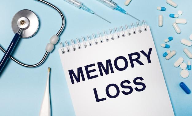 Op een lichtgrijs oppervlak, een stethoscoop, een elektronische thermometer, pillen, spuiten en een notitieboekje met de tekst memory loss
