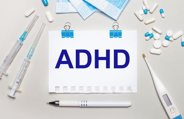 Op een lichtgrijze achtergrond, blauwe medische maskers, spuiten, een elektronische thermometer, pillen, een pen en een notitieboekje met de inscriptie adhd. medisch concept