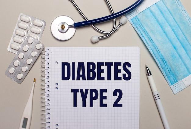 Op een lichtgrijze achtergrond, een lichtblauw wegwerpmasker, een stethoscoop, een elektronische thermometer, pillen, een pen en een notitieboekje met de tekst diabetes type 2. medisch concept