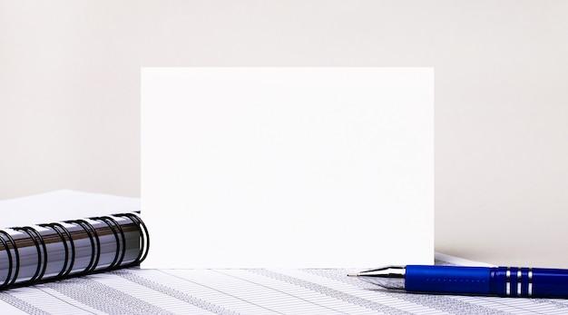 Op een lichtgrijze achtergrond, een notitieboekje, een blauwe pen en een vel papier met een plek om tekst in te voegen. sjabloon. bedrijfsconcept