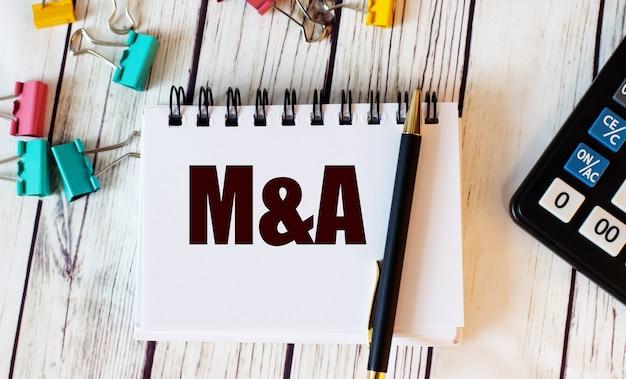 Op een lichthouten tafel liggen een rekenmachine, veelkleurige paperclips en een notitieboekje met een pen en het woord m and a