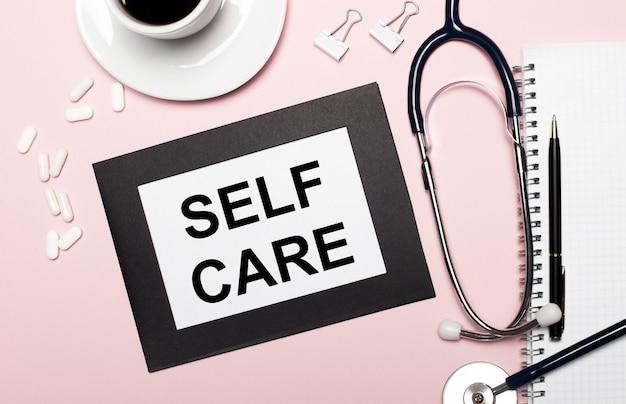 Op een lichtroze achtergrond, een notitieboekje met een pen, stethoscoop, witte pillen, paperclips en een vel papier met de tekst self care