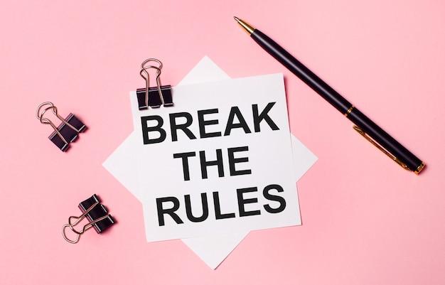 Op een lichtroze achtergrond, zwarte paperclips, zwarte pen en wit notitiepapier met de woorden break the rules. plat leggen