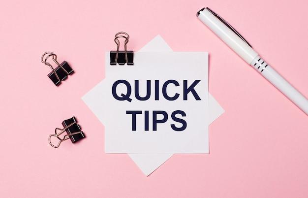 Op een lichtroze achtergrond, zwarte paperclips, zwarte pen en wit notitiepapier met de woorden quick tips. plat leggen