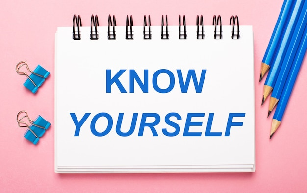 Op een lichtroze ondergrond, lichtblauwe potloden, paperclips en een wit notitieboekje met de tekst know yourself