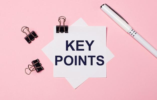 Op een lichtroze ondergrond, zwarte paperclips, een witte pen en wit notitiepapier met de tekst key points. plat leggen