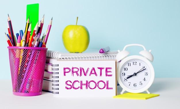 Op een lichttafel staan boeken, briefpapier, een witte wekker, een appel. ernaast ligt een notitieboekje met de tekst private school. educatief concept.
