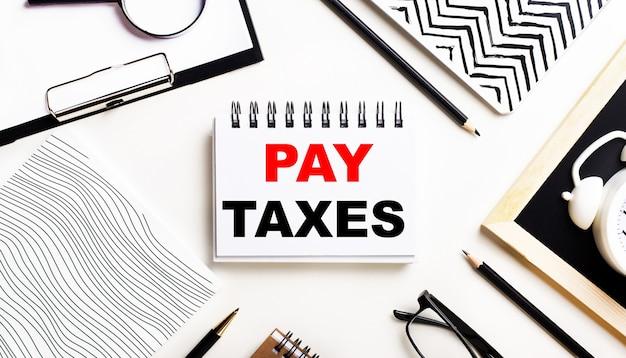 Op een lichttafel staan notitieboekjes, een vergrootglas, een wekker, een bril en een pen. en in het midden is een notitieboekje met de tekst pay taxes.