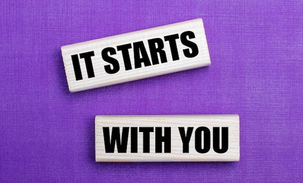 Op een lila heldere ondergrond, lichte houten blokken met de tekst it starts with you