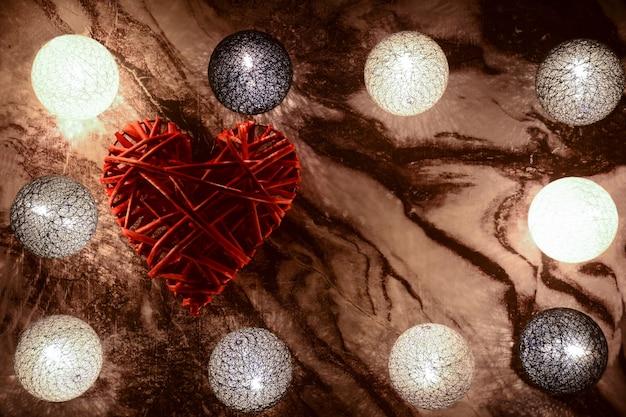 Op een marmeren achtergrond liggen gloeiende decoratieve ballen rond de omtrek en een groot rood decoratief hart aan de linkerkant binnenin. aan de rechterkant is er een plaats voor een inscriptie voor verschillende feestdagen.