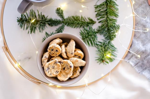 Op een marmeren blad met een gouden rand staan twee grijze kopjes thee en een chocoladekoekje. een traktatie voor de kerstman. kerstboomtak met slingers versieren de nieuwjaarskaart. kopieer ruimte