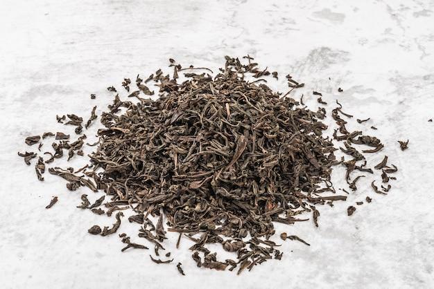 Op een marmeren tafel staat gedroogde thee opgestapeld.