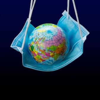 Op een medisch verband, als op een hangmat, is een model van de planeet aarde, het concept van een wereldwijde virale epidemie en bescherming