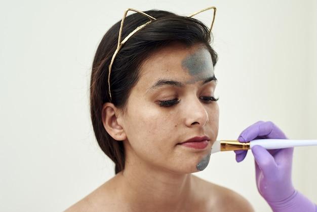 Op een mooie jonge vrouw wordt een grijs moddermasker aangebracht. schoonheidsspecialiste procedures. gezichtsverzorging, poriënverstrakking en hydratatie met natuurlijke cosmetische crèmes.
