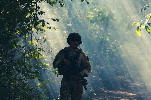 Op een natuurlijke achtergrond, een legersoldaat in gevechtsuniformen met een aanvalsgeweer of geweer.