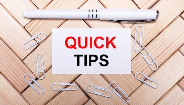 Op een ondergrond van houten blokken, een witte pen, witte paperclips en een witte kaart met de tekst quick tips