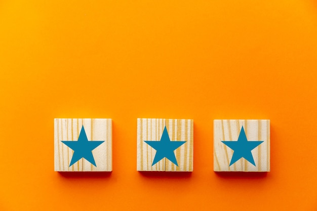 Op een oranje achtergrond is een driesterrenteken afgebeeld op houten kubussen. concepten zoals klantervaring, tevredenheidsonderzoek, evaluatie, beoordeling verhogen en topscore voor uitstekende services.
