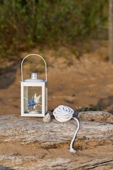 Op een oud houtblok in een lantaarn in nautische stijl, een schaal en een nautisch touw