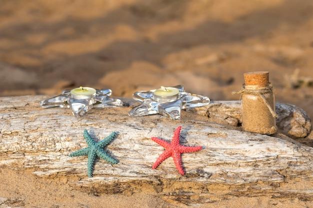 Op een oude houtblok in het zand, zeester en zand in een fles
