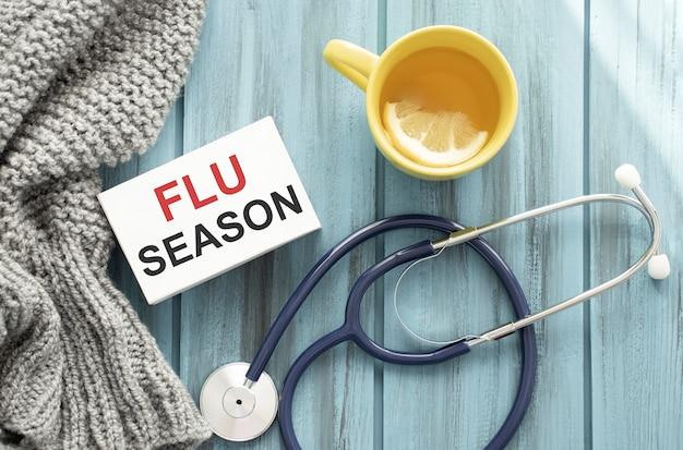 Op een paarse achtergrond een stethoscoop met gele lijst met tekst flu season
