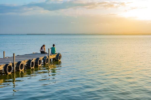 Op een pier, paar zittend op hun rug