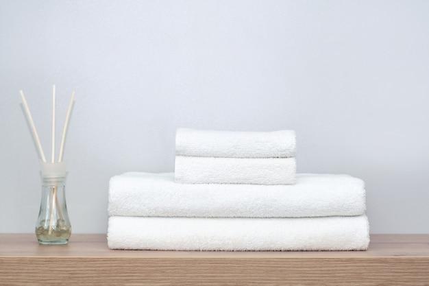 Op een plank in de badkamer liggen witte handdoeken van verschillende afmetingen netjes opgevouwen en daarnaast staat een glazen pot met geurende balletjes en houten stokjes. het concept van spa, orde in huis, textiel.