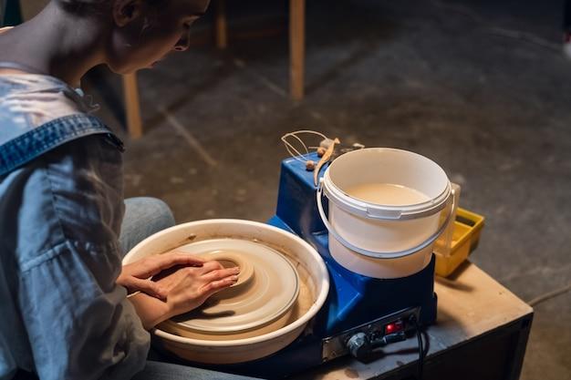 Op een pottenbakkersschijf maakt een jonge pottenbakker een voorbereiding voor een pot van klei.