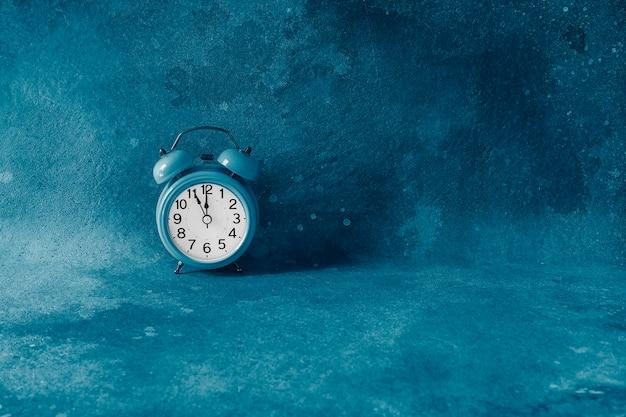 Op een retro-wekker om vijf minuten voor middernacht. vijf minuten voor het begin van een nieuwe dag of nieuw jaar. laatste aftellen. afgezwakt in klassiek trendy blauw. copyspace.