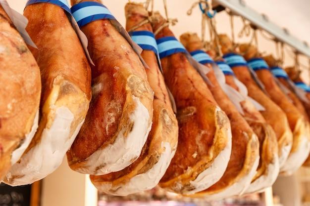 Op een rij hangen jamon in de winkel. traditioneel mediterraan eten. detailopname.
