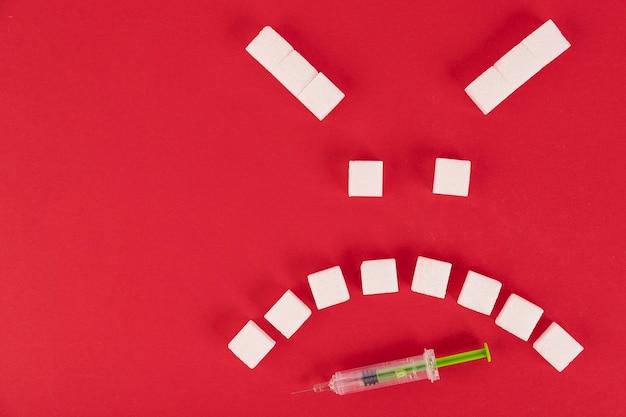Op een rode achtergrond, blokjes witte suiker in de vorm van een kwaadaardige emoticon en een insulinespuit. ruimte kopiëren.