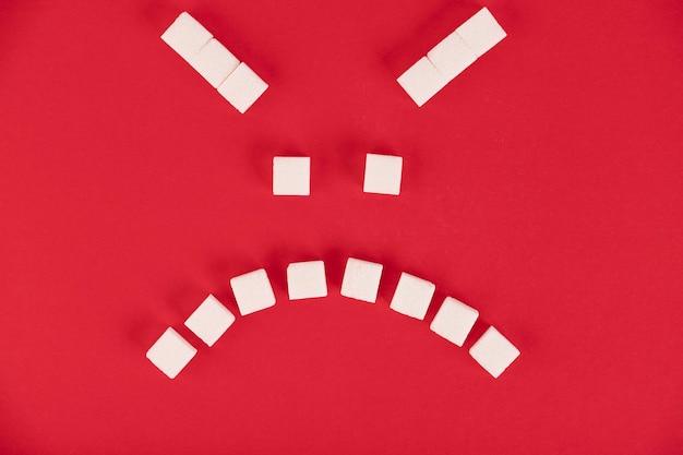Op een rode achtergrond, blokjes witte suiker, in de vorm van een kwaadaardige emoticon. ruimte kopiëren.