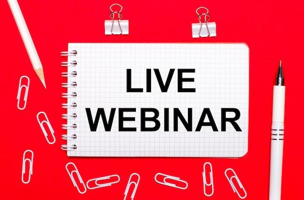 Op een rode achtergrond een witte pen, witte paperclips, een wit potlood en een notitieboekje met de tekst live webinar. uitzicht van boven