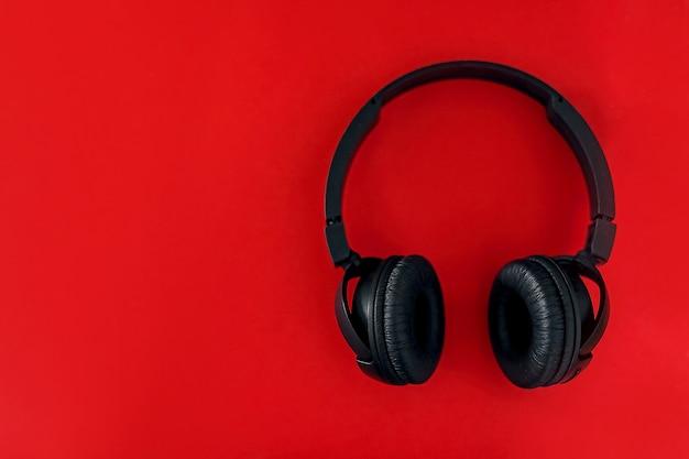 Op een rode achtergrond staan zwarte koptelefoons. plat leggen.