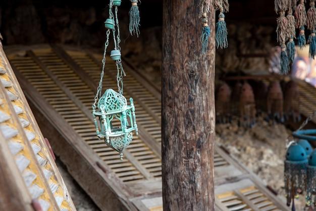 Op een rommelmarkt hangt een oude metalen lamp of kandelaar.